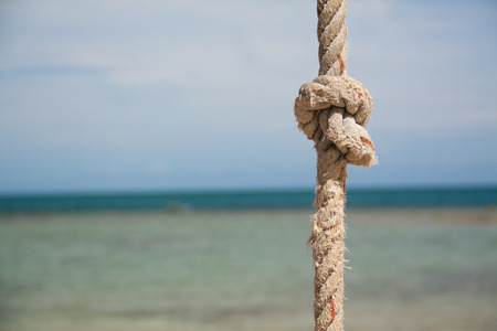knot on the rope on the background of the blue sea photo
