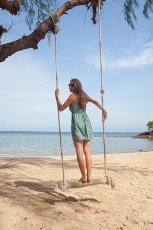 young woman playing the swing on beach photo