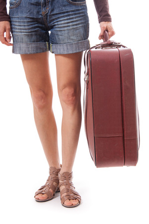 female legs in shorts and suitcase in hand, isolated on white  photo