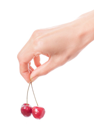 hand holding the two fresh cherries, isolated  on white background photo
