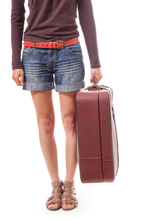 female legs in shorts and suitcase in hand, isolated on white background photo