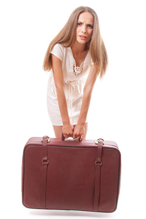 woman lifts a heavy suitcase, isolated on white background photo