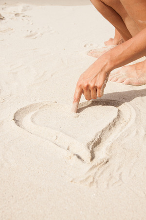 Heart drawn in the sand. Beach background. photo