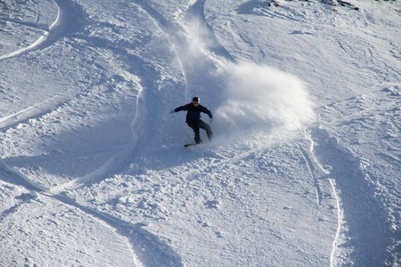 Snowboard freerider in the snowy mountains photo