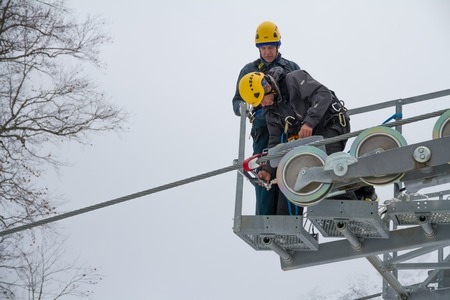 SOCHI, RUSSIA - DECEMBER 12, 2013: Workers repairing the ski lift in mountain resort Rosa Khutor. Editorial