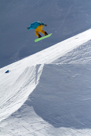 Snowboarder jumps in Snow Park,  mountain ski resort photo