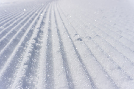 groomer: Fresh snow groomer tracks on a mountain ski piste, background