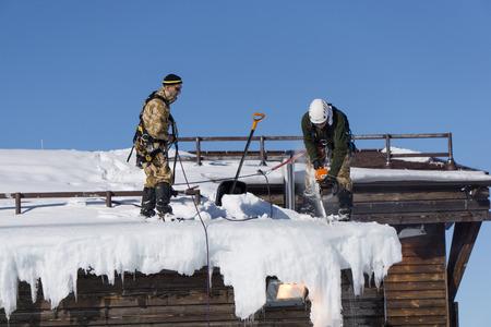 Sochi, Russland - 22. Januar 2015: Industriekletterer nehmen Sie den Schnee und Eiszapfen vom Dach Editorial