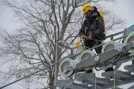mounter: SOCHI, RUSSIA - DECEMBER 12, 2013: Workers repairing the ski lift in mountain resort Rosa Khutor. Editorial