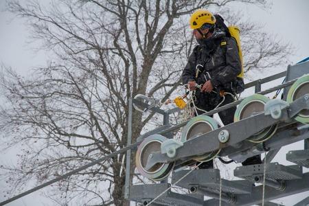 assemblage: SOCHI, RUSSIA - DECEMBER 12, 2013: Workers repairing the ski lift in mountain resort Rosa Khutor. Editorial