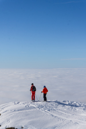 雲の上の山の頂上に立っている 2 つのスキーヤー 写真素材