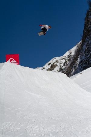 quicksilver: SOCHI, RUSSIA - MARCH 22, 2014: Snowboarder jumps in Snow Park,  mountain ski resort Rosa Khutor.
