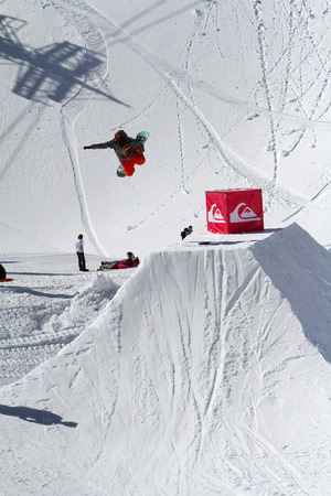 SOCHI, RUSSIA - MARCH 22, 2014: Snowboarder jumps in Snow Park,  mountain ski resort Rosa Khutor.