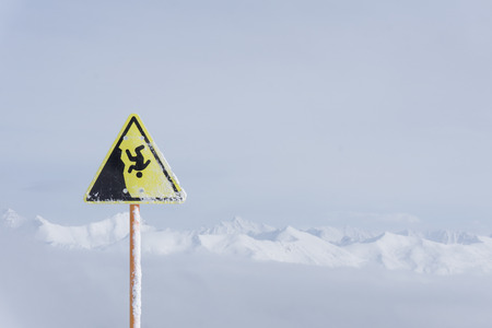 steep cliff sign: danger steep cliff mountain sign, mountains and cloudy sky Stock Photo