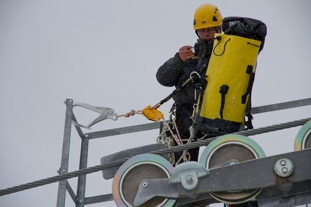 mounter: SOCHI, RUSSIA - DECEMBER 12, 2013: Workers repairing the ski lift in mountain resort Rosa Khutor. Editorial