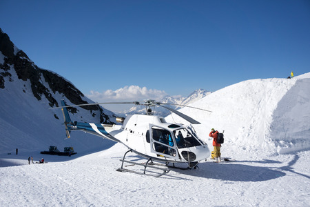 skiing accident: White rescue helicopter parked in the snowy mountains