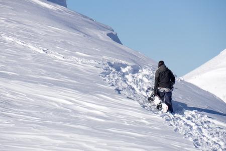 freeride: Snowboarder climbing a snowy mountain, freeride