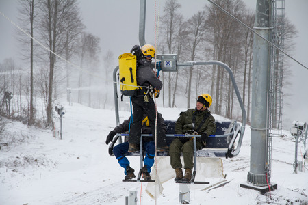 mounter: SOCHI, RUSSIA - DECEMBER 12, 2013: Rescuers rehearse rescue on the ski lift. Mountain resort Rosa Khutor.