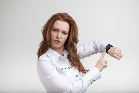 Young businesswoman in white blouse, looking at her watch