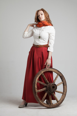 mediaeval: Young woman in long red skirt standing near the wheel of the cart Stock Photo