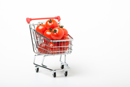 shopping cart with cherry tomatoes, isolated on white background photo