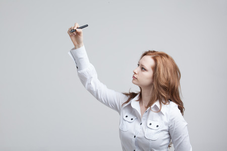 grey background: young woman with pen  writes or shows on grey background Stock Photo