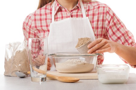 knead: young woman knead the dough, isolated on white background Stock Photo