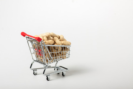 carro supermercado: unshelled peanuts in the supermarket trolley, isolated on white background