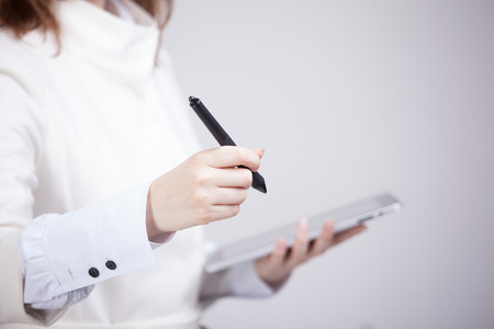 stylus: woman holding a tablet and black stylus Stock Photo