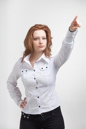 dedo indice: Empresaria joven en camisa blanca dedo �ndice apuntando Foto de archivo