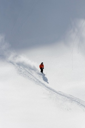 heli: Skier in deep powder, extreme freeride in the mountains
