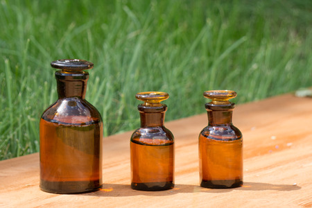 brown bottles: little brown bottles on booden board and green grass