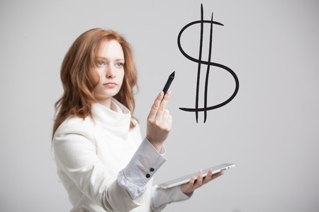 grey background: Young woman drawing dollar symbol on grey background