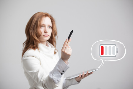 stylus pen: Young Businesswoman holding tablet and pen, battery level icon