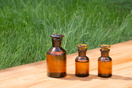 grunge bottle: little brown bottles on booden board and green grass