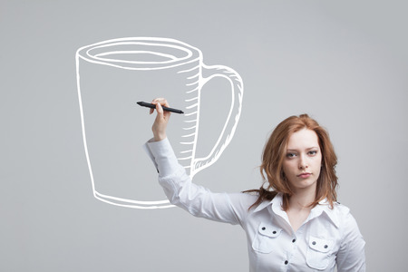 stylus: young woman with pen draws a Cup of coffee on grey background Stock Photo