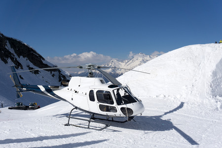 heli: White rescue helicopter parked in the snowy mountains