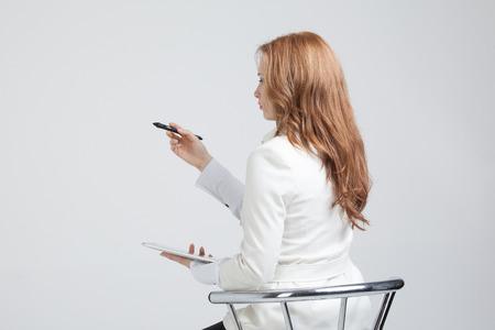 灰色背景: ペンを持つ若い女性の書き込みや灰色の背景は、