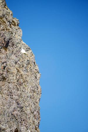 steep: steep rock and blue sky