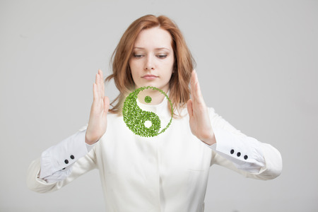 ideology: Young woman holding green plant ying yang symbol