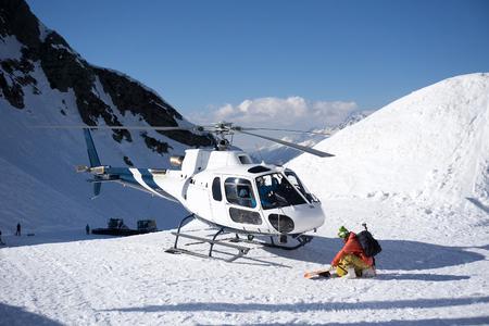 Bianco elicottero di salvataggio parcheggiata tra le montagne innevate Archivio Fotografico
