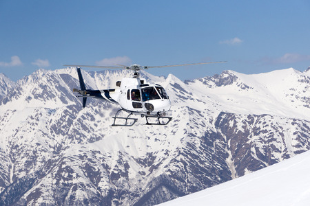 snowy mountains: White rescue helicopter in the snowy mountains