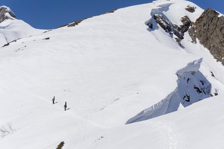 off piste: Snowboarders walking uphill for freeride, extreme sport