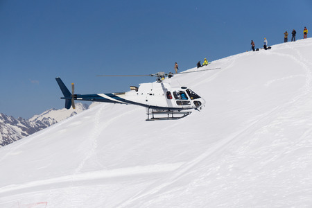 skiing accident: White rescue helicopter in the snowy mountains