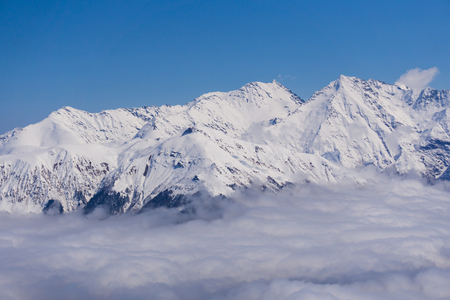 heli: View on winter snowy mountains and blue sky above clouds, Krasnaya Polyana, Sochi, Russia