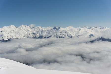 snowy mountains: View on winter snowy mountains and blue sky above clouds, Krasnaya Polyana, Sochi, Russia