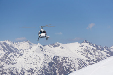 White rescue helicopter in the snowy mountains