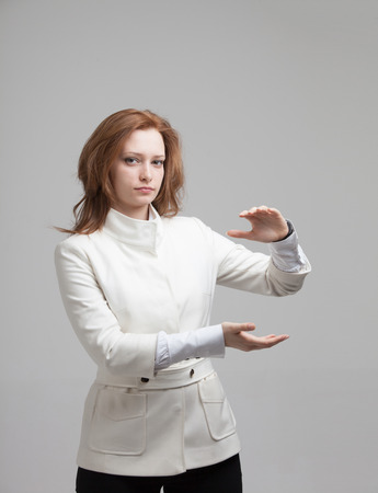 qigong: Woman holding something in hands on gray background Stock Photo