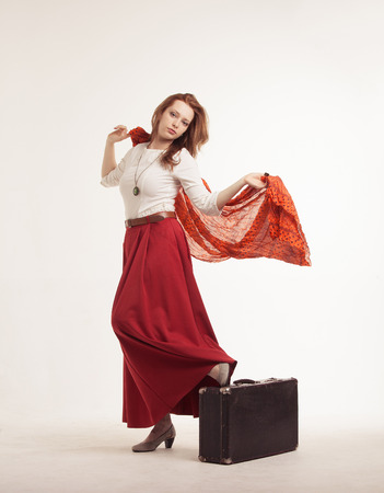 mujer con maleta: young woman in skirt dancing with a red handkerchief and suitcase Foto de archivo