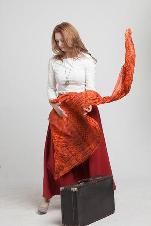 giovane donna in ballo gonna con un fazzoletto rosso e la valigia